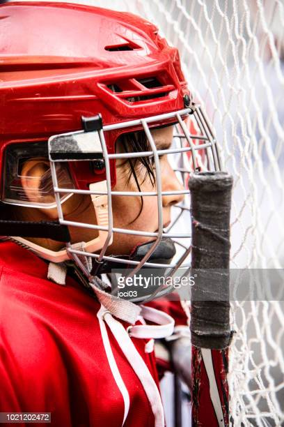 young girl ice hockey player in red equipment - center ice hockey player stock pictures, royalty-free photos & images