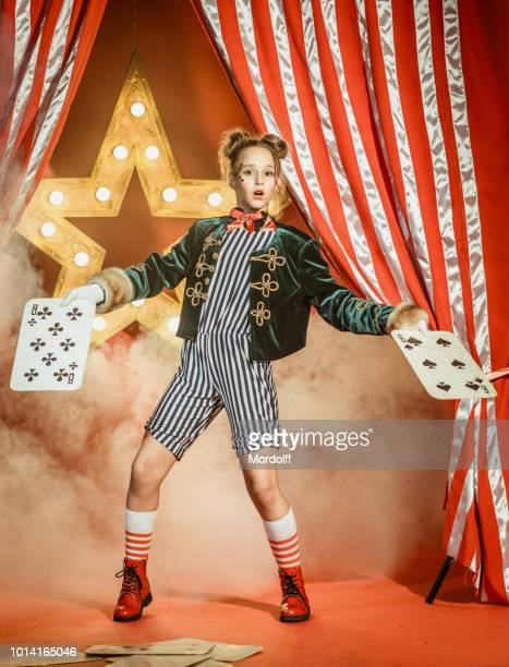 young girl illusionist with playing cards. card trick is failed - circus stock pictures, royalty-free photos & images
