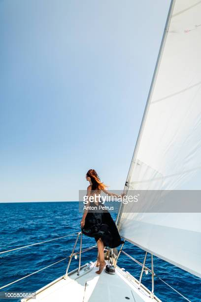 Young girl in a black summer dress on a white yacht