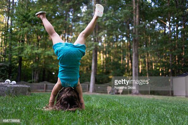young girl in a blue dress doing handstands in the backyard - girl in dress doing handstand stockfoto's en -beelden