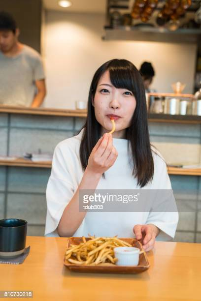 Young girl in a cafe eating french fries