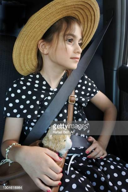 young  girl in a car seat traveling by car - rafael ben ari stockfoto's en -beelden