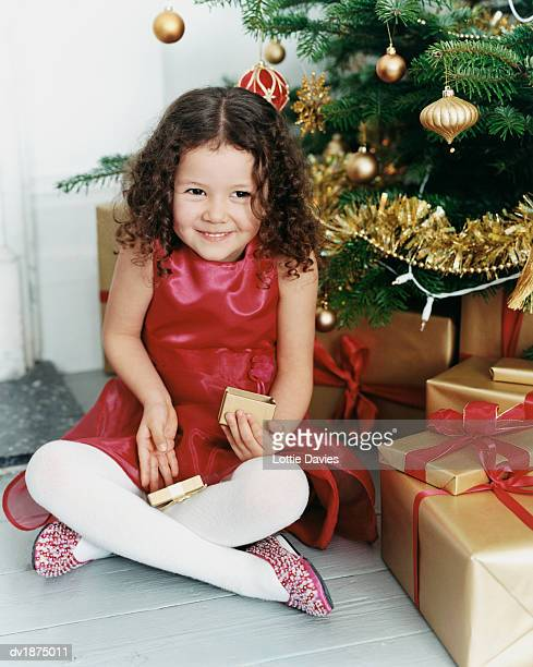 young girl in a dress sits cross-legged on the floor by a christmas tree, opening a gift box - little girls dressed up wearing pantyhose stock photos and pictures