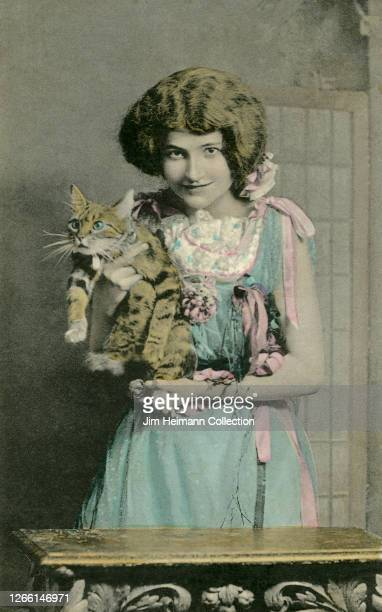A young girl in a frilly dress holds a kitten which looks like it wants to escape circa 1902