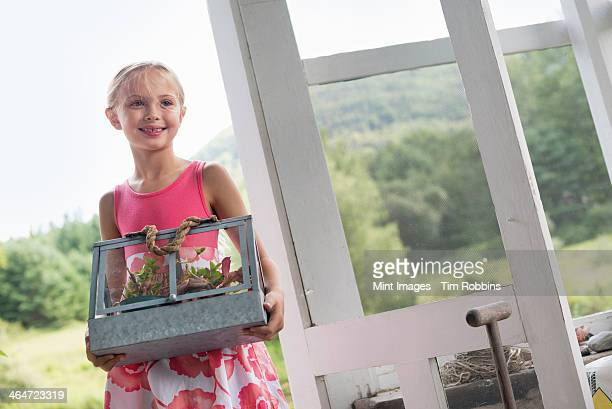 A young girl in a kitchen wearing a pink dress.  Carrying a terrarium containing small plants.