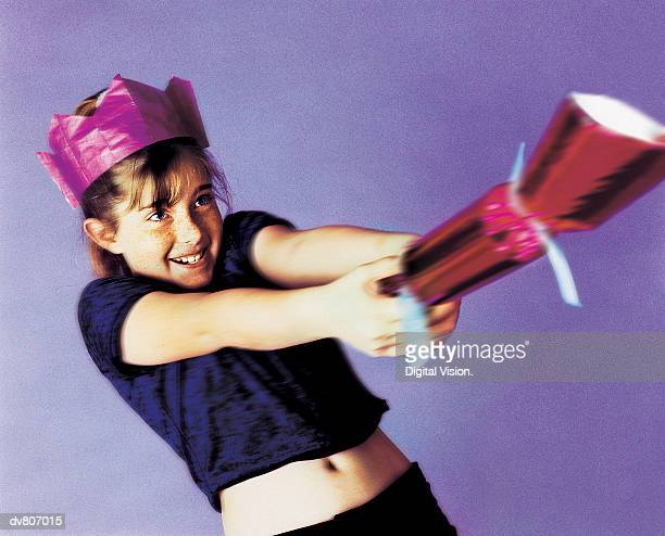 Young Girl in a Party Hat Pulling a Christmas Cracker