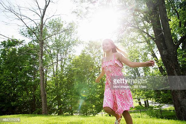 A young girl in a pink patterned sundress running across the grass under the trees in a farmhouse garden.