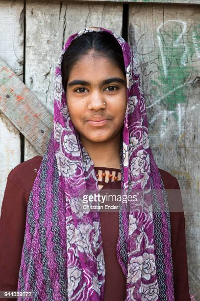 A young girl in a purple traditional costume who is standing in front of a door of a barn in a poor neighbourhood on March 28 2013 in Bijapur India...