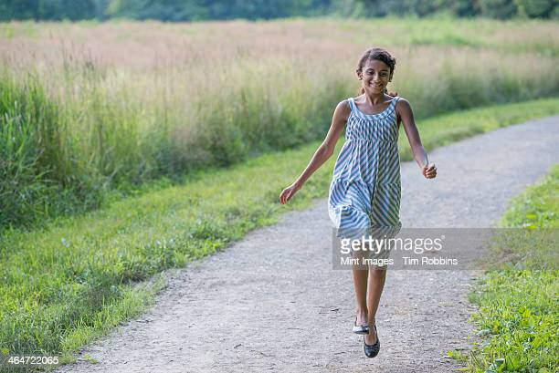 A young girl in a summer dress walking along a path.