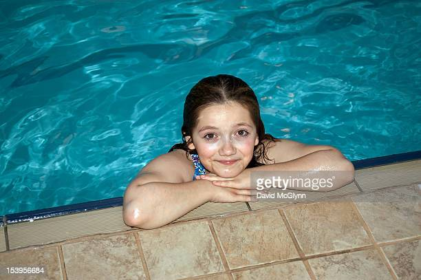 Young girl in a swimming pool, leaning on the edge