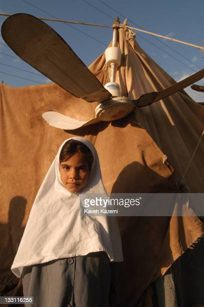 A young girl in a veil and school uniform who lost her home after the earthquake struck the city stands outside the tent where she lives with her...