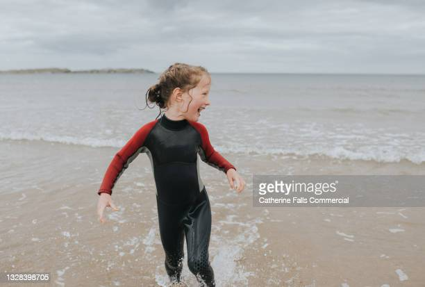 young girl in a wet suit paddles in the sea - sea stock pictures, royalty-free photos & images