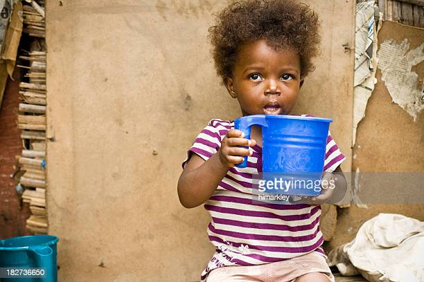 A young girl in Africa holding a blue bucket
