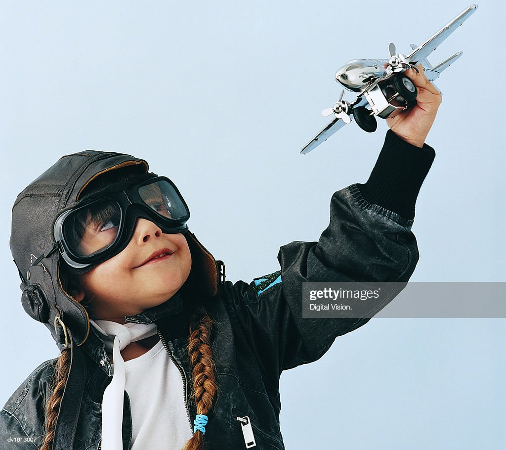 Young Girl in an Aviator Costume Playing With a Toy Aircraft : Stock Photo