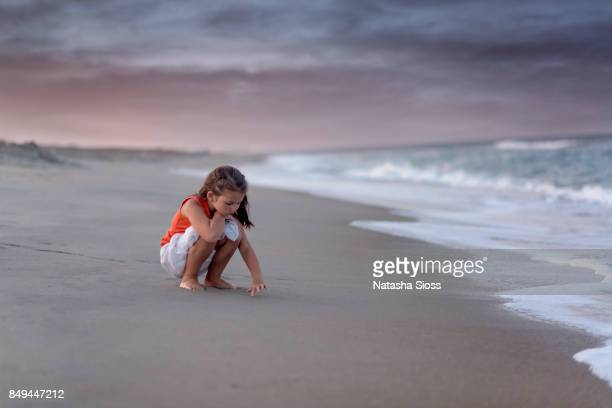 young girl in an orange tanktop on the beach at sunset - rivage photos et images de collection