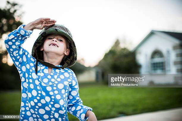 young girl in army helmet a saluting