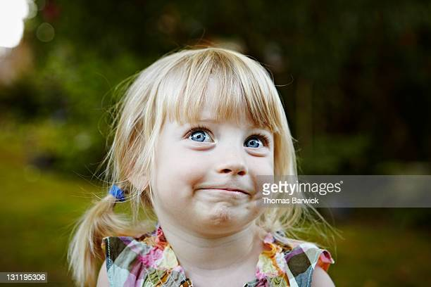young girl in backyard smiling looking up - naughty america stock pictures, royalty-free photos & images