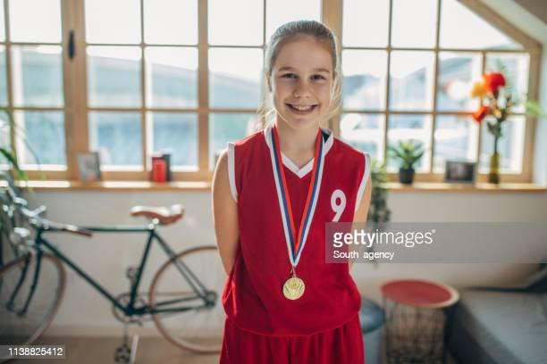 junges mädchen im basketball-trikot - medaillengewinner stock-fotos und bilder