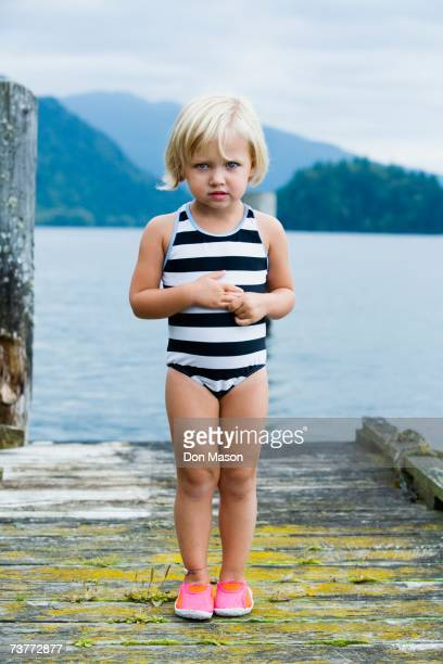 Young girl in bathing suit standing on wooden pier