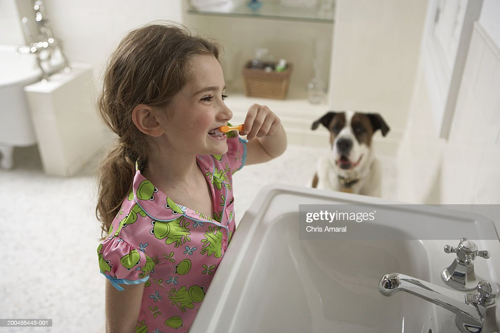Young girl (8-10) in bathroom brushing her teeth with dog : Stock Photo