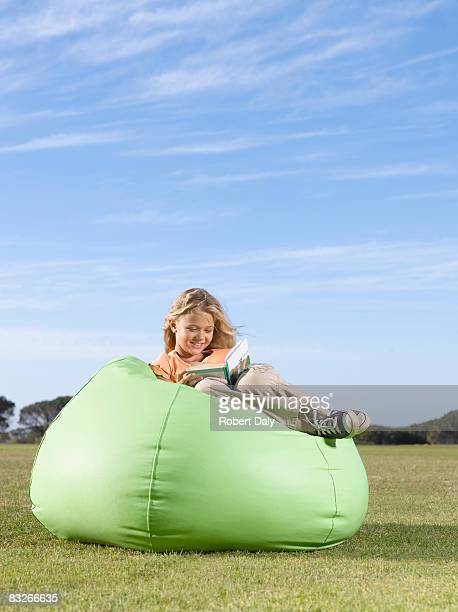 Young girl in bean bag reading outdoors