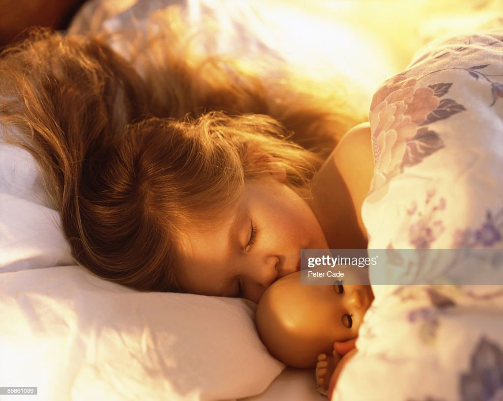 Young girl in bed asleep with doll : Stock-Foto