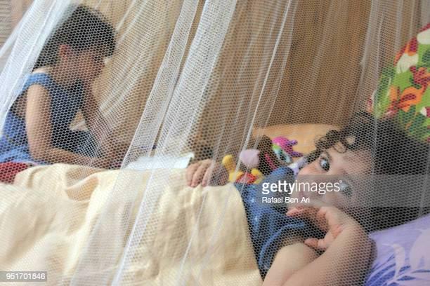 young girl in bed listen to her sister reading a story before bedtime - rafael ben ari fotografías e imágenes de stock
