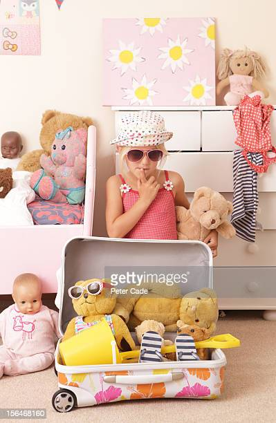 Young girl in bedroom packing suitcase with toys