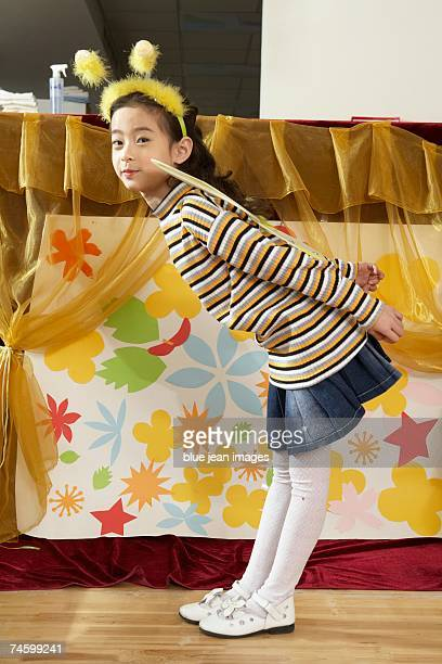 young girl in bee costume leans over. - little girls bent over stock photos and pictures