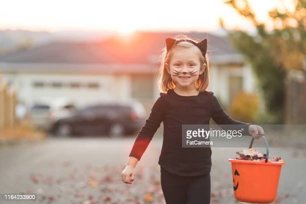 young girl in black cat costume goes trick or treating - halloween cats stock pictures, royalty-free photos & images