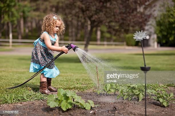 Jeune fille en robe bleue arroser le jardin