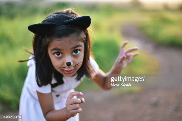 young girl in cat costume acting like a cat - cat costume stock photos and pictures