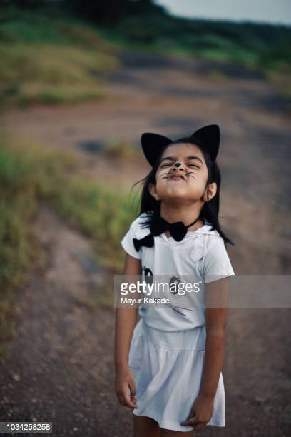 Young girl in cat costume making scary expressions