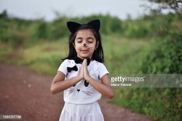 young girl in cat costume meditating - cat costume stock photos and pictures