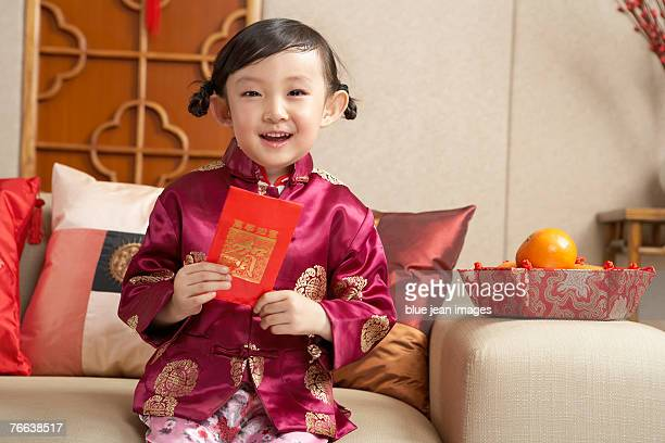 A young girl in Chinese traditional clothing sitting on the sofa celebrates Chinese New Year.