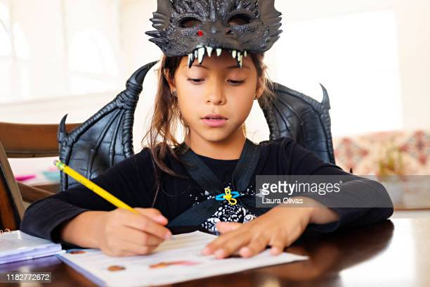 Young Girl In Costume Doing Homework