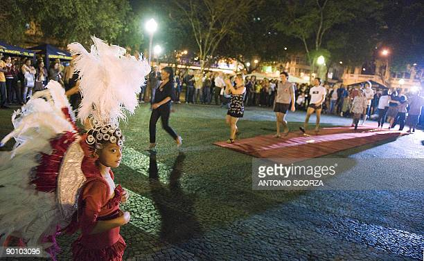 A young girl in costume stands by as Brazilian prostitutes and supporters present creations by DASPU a local fashion label run by prostitutes in...