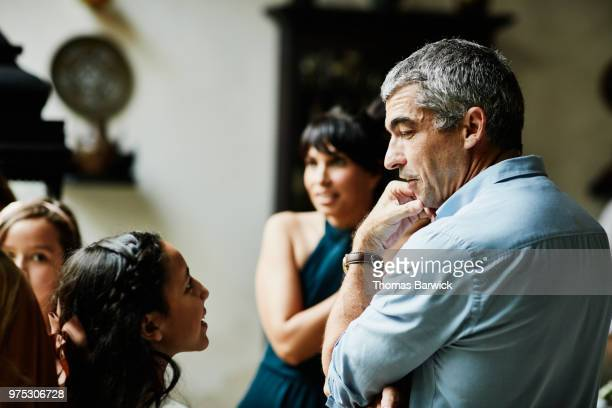 Young girl in discussion with uncle in dining room during family celebration