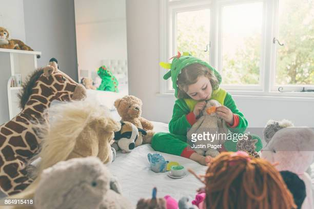 Young Girl in dragon costume - having teddy bear picnic
