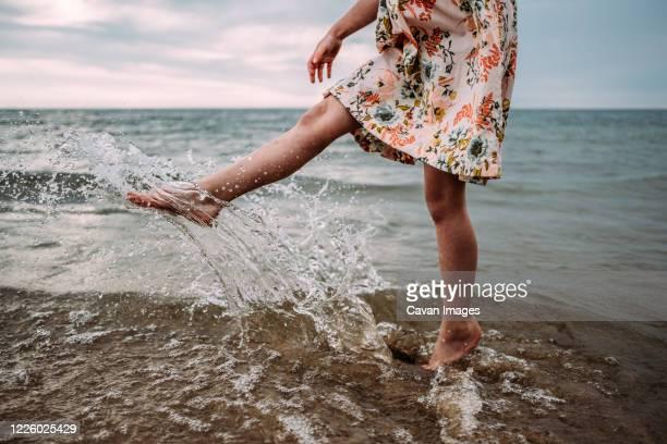 young girl in dress splashing water in lake michigan - chutar imagens e fotografias de stock