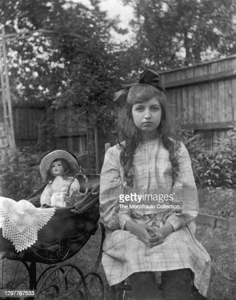 Young girl in dress with large ribbon in her hair sitting in garden beside toy pram with a porcelain doll seated inside draped over the pram is a...