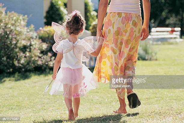 Young Girl in Fairy Fancy Dress Walking in the Garden With Her Mother Holding Hands