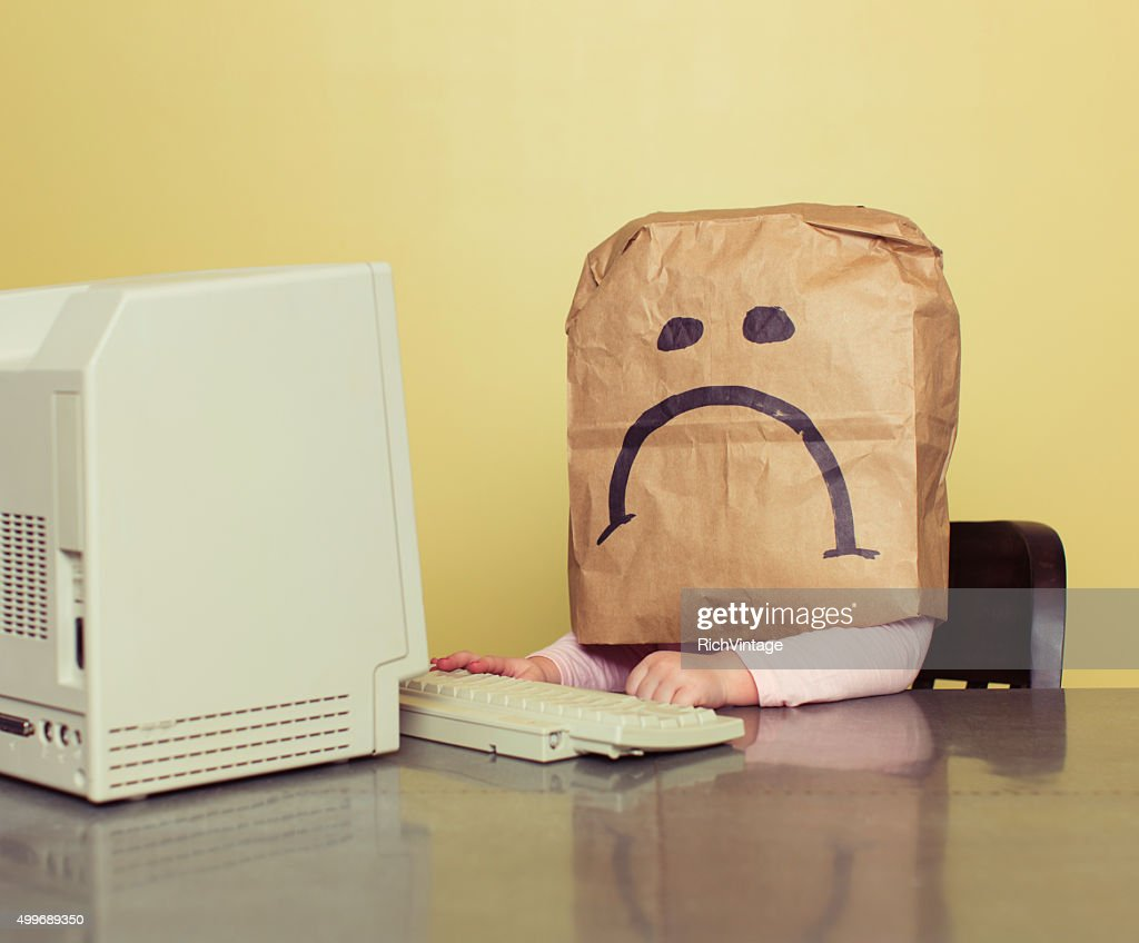 Young Girl in Front of Computer with Brown Bag Frown : Stock Photo