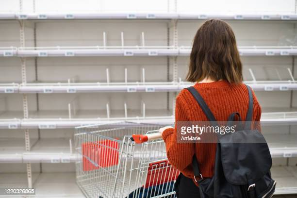 young girl in front of empty shelf in a supermarket, panic buying and hoarding concept - sold out stock pictures, royalty-free photos & images