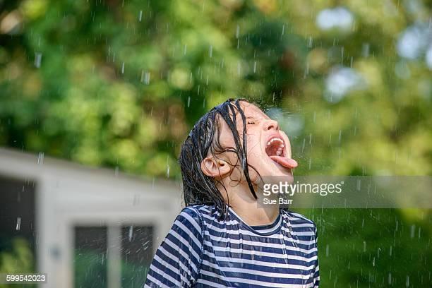 Young girl in garden, catching falling water in mouth