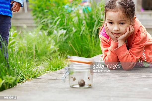 Young girl in garden watching jar of snails