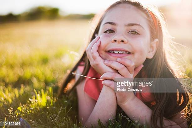 young girl in grass smiling - brace stock pictures, royalty-free photos & images