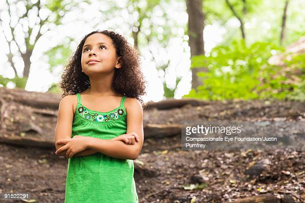 young girl in green looking up in a forest