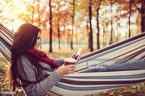 Young girl in hammock texting