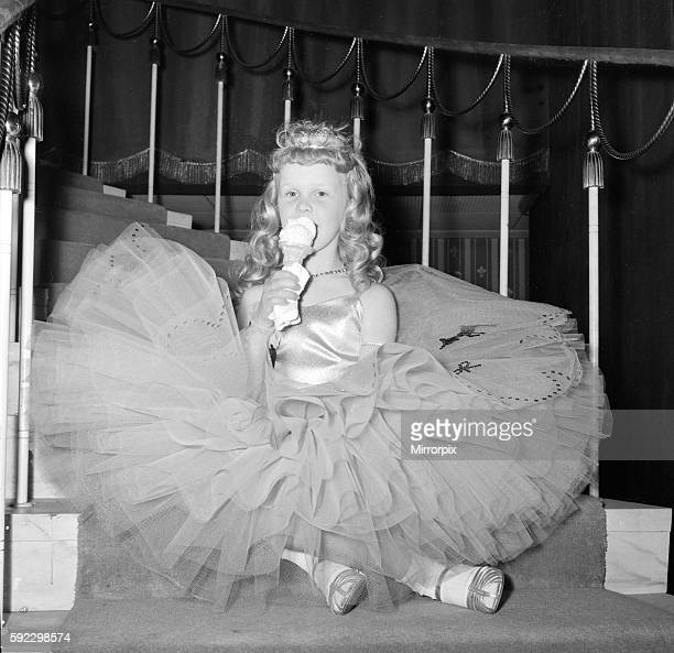 A young girl in her crinoline style ball gown takes an ice cream break during the Junior Old Time Dancing Contest at the Hammersmith Palais 4th June...